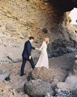 Bride Leading Groom Through Rocky Beach