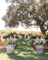last row ceremony chair decorations barrels topped with floral arrangements