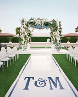59 wedding arches that will instantly upgrade your ceremony martha glamorous white flower wedding arch with aisle monogram junglespirit Images