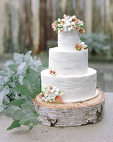 Three-Tiered White Wedding Cake with Wood-Like Icing and Orange and White Flowers