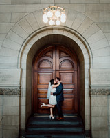 city hall wedding bride and groom kissing in front of wooden door