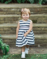 flower girl wearing navy striped dress and sneakers