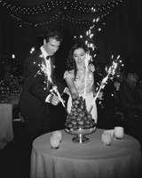 couple putting sparklers in their cake