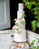 four tiered white frosted cake with sugar flowers