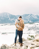 destination engagement couple snow capped mountain background