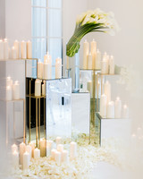 mirrored boxes with various white candles and white flowers