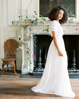 bride standing in front of white fireplace decorated with floral garland