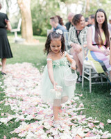 flower girl in green dress dropping petals