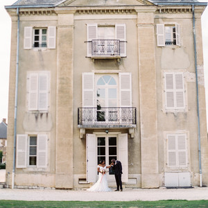 couple poses outside in front of wedding venue