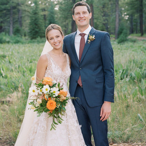 bride and groom smiling in front of forest