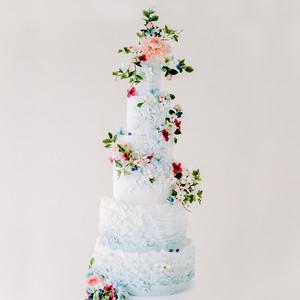 light blue wedding cake adorned with vibrant sugar flowers