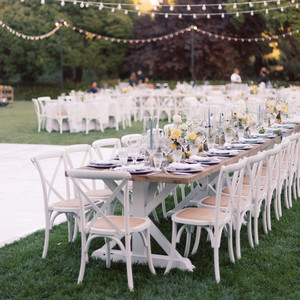 wooden table string light outside wedding reception setup