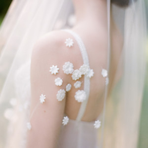 bride wearing veil with small flower appliqués