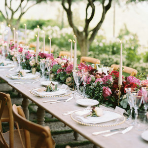 allie and joe italy wedding long reception table decorated with pink and red flowers and gold candle sticks