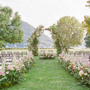 julia mauro wedding ceremony setting with floral arch and chairs