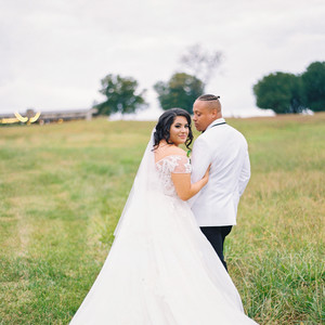 bride and groom pose for portrait outside at farm wedding venue