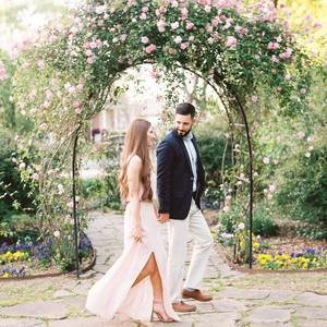 couple walking under floral arch engagement