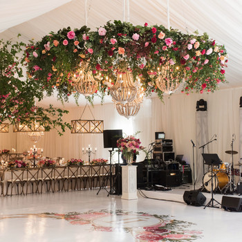 wedding chandelier with roses and greenery wood beams