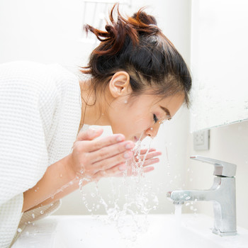 woman splashing water washing face