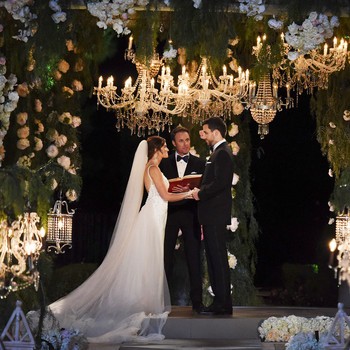 chris harrison officiating wedding surrounded by floral decor and chandeliers
