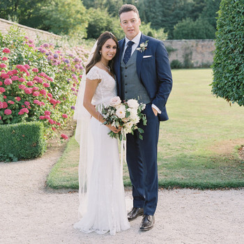bride and groom pose for portrait in garden venue