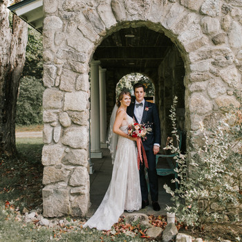 bride and groom standing under stone arch
