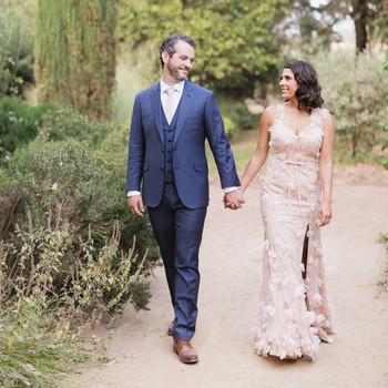 bride and groom hold hands walking down pathway outdoors