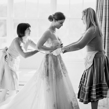 women helping bride get dressed