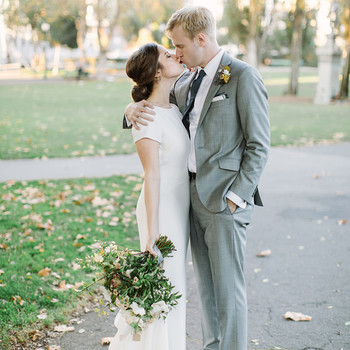 bride and groom kissing on walkway outside