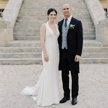 bride and groom pose outside Chateau La Louviere wedding venue