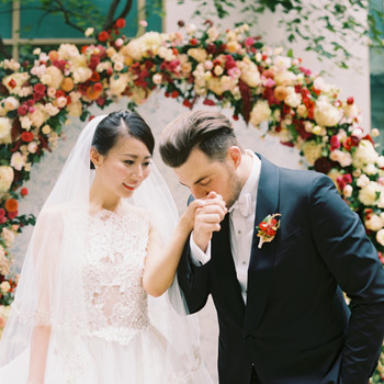 groom kisses bride's hand next to floral arch
