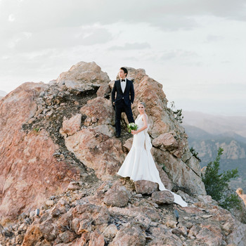 bride and groom posing on cliff