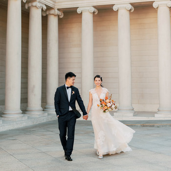 wedding couple holding hands outside museum