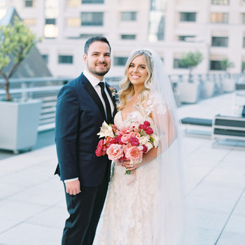 bride and groom smiling outside at wedding venue