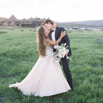 bride groom kiss grass field outside venue lodge