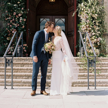 wedding couple kiss outdoors church steps floral arch doorway