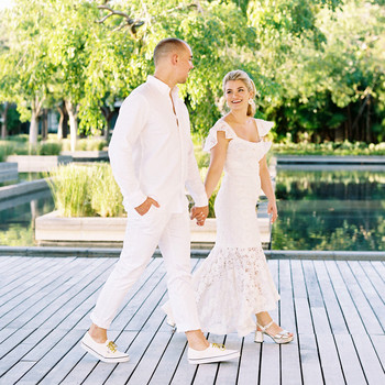 bride and groom holding hands walking on wooden path next to water