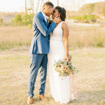 bride and groom wedding portraits kissing in field