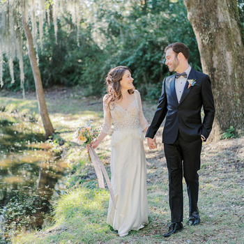 bride and groom smiling holding hands outside under draping willow tree