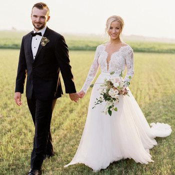 groom and bride walking outdoors grass field wedding attire