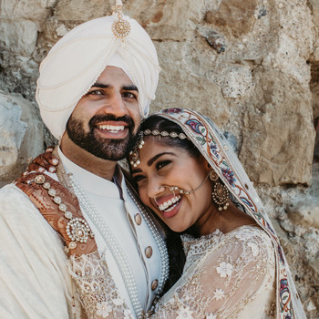indian wedding bride holding groom smiling