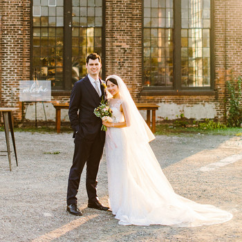 bride and groom posing at golden hour outside industrial wedding space