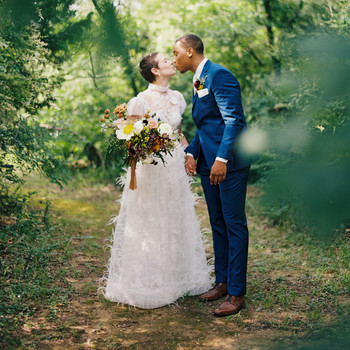 Wife and husband kissing in wooded area