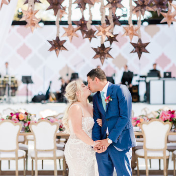bride and groom kiss under hanging stars decor