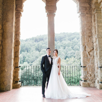 groom and bride pose at 20th century building balcony mountain view