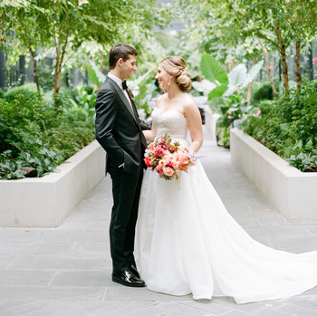 bride and groom looking at one another in courtyard
