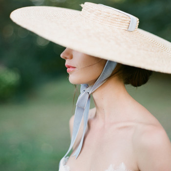 bride wearing large hat with blue ribbon