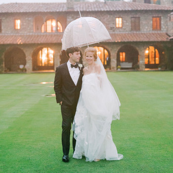 bride and groom outside wedding venue under umbrella