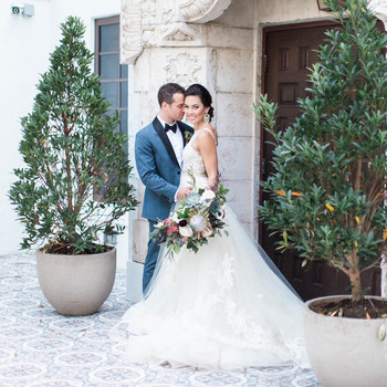 bride and groom pose outside under stone archway