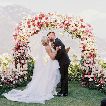 allie and joe italy wedding couple kissing beneath floral arch